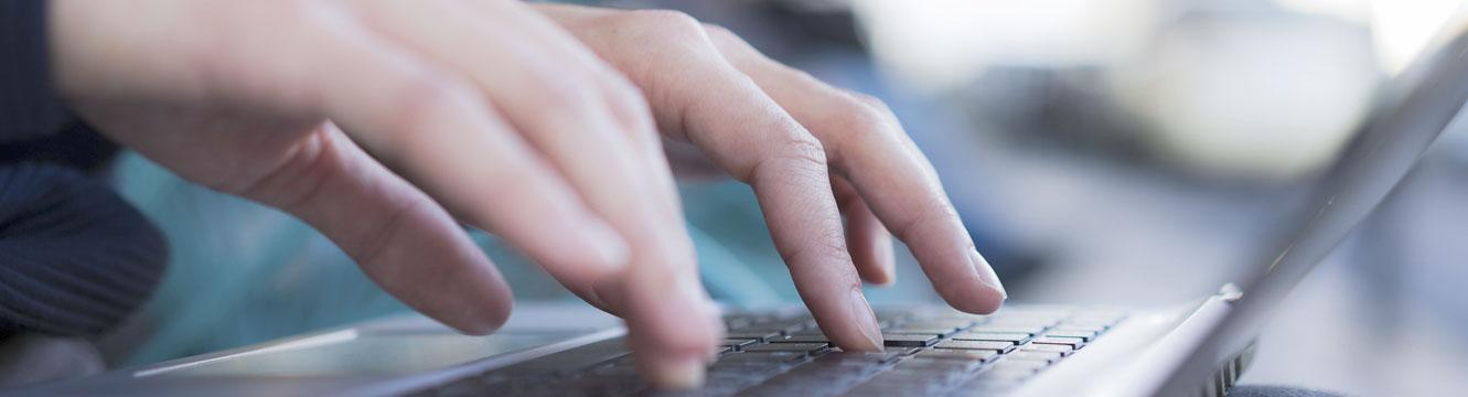 Un recruteur rédige un email depuis son ordinateur pour demander un renseignement.