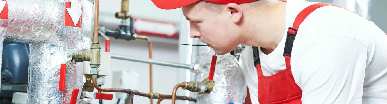 Un Plombier chauffagiste inspecte le système de chauffage d'une chaudière