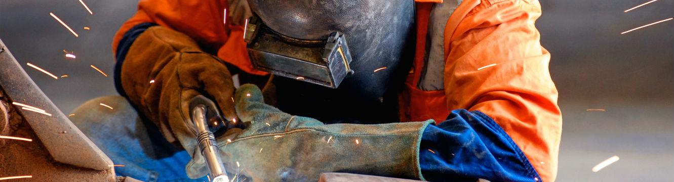Un ouvrier soudeur assemble des pièces en métal