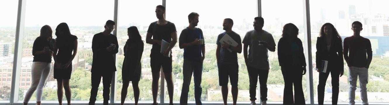 une équipe de travail se tient en ligne devant une baie vitrée